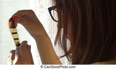 Woman Unrolling a Color Filmstrip - Woman is unrolling a...