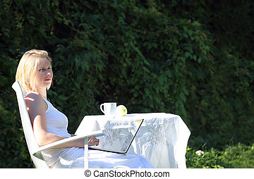 Woman with laptop outdoors - Woman working on a laptop...