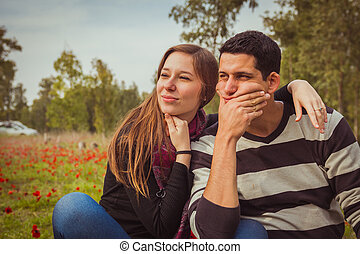 Young couple looking away with a thoughtful look while sitting on the grass in a field of red poppies