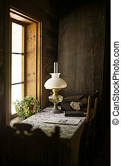 Ancient house interior with lamp and table.