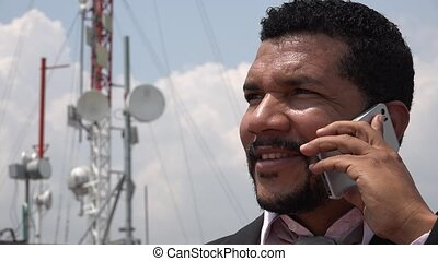 Man Talking On Cell Phone Near Cell Tower