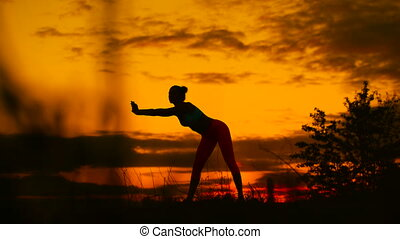 Silhouette of woman standing at yoga pose during an amazing sunset.
