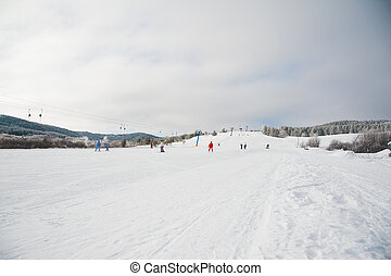 People skiing and snowboarding on a slope