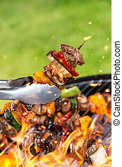 Meat skewer on grill - Full grill and meat skewer being hold...