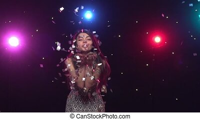 Young woman blowing with hands glitter confetti. Slow motion...