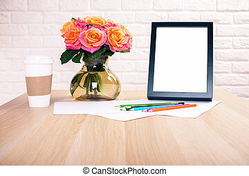 Desktop with frame and flowers - Front view of wooden...