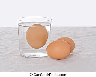Testing fresh eggs - rotten one, floating in water...