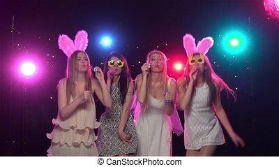 Girlfriends blowing soap bubbles at bachelorette party. Slow motion