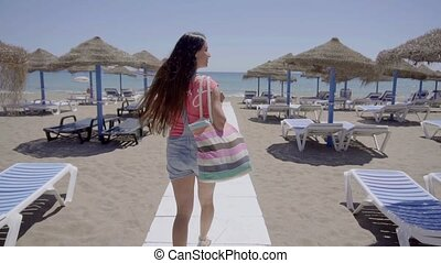 Cute woman walking on boardwalk to beach - Cute single...