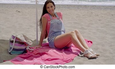 Pretty woman on blanket in shade on beach - Pretty smiling...