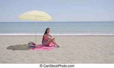 Young woman waving hand while on beach blanket - Cute young...