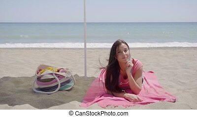 Cute woman laying down on beach blanket - Single cute woman...