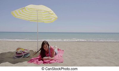 Woman on phone call at beach under umbrella - Woman on phone...
