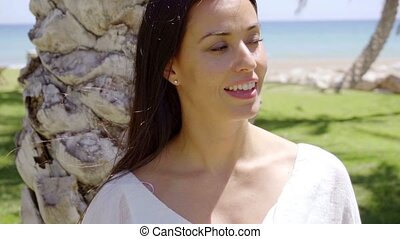 Smiling woman near green grass and palm trees - Pretty...