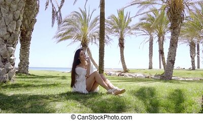 Smiling cute woman sitting on green grass