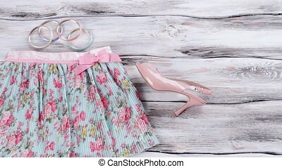 Floral skirt and salmon heels. Sunglasses, bracelets and...