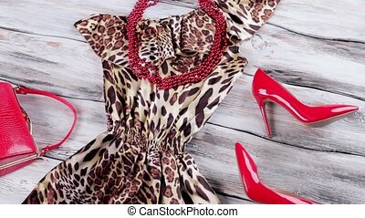 Dress with dark bead necklace. Bright heels and red...