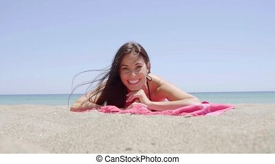 Excited attractive young woman lying on a beach - Low angle...