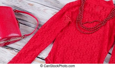 Red top and glossy shoes. Bead necklace and handbag. Woman's...