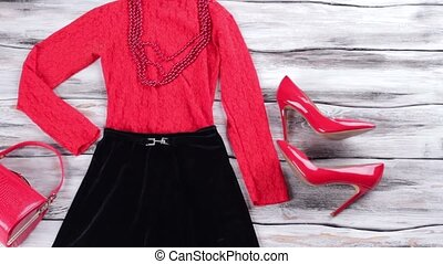 Dark skirt and red top. Glossy heels and bead necklace....