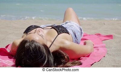 Young woman soaking up the summer sun lying sunbathing on a...