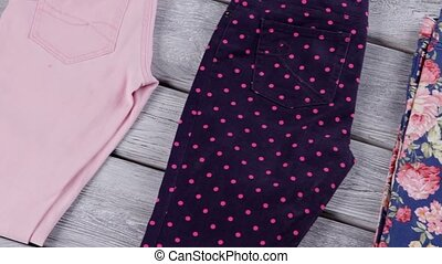 Pink and dark navy pants. Stylish trousers on wooden...
