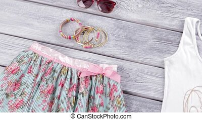 Sunglasses and floral skirt. Skirt with print and bracelets....
