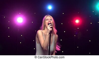 Blonde girl singing emotionally into a retro microphone....