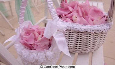 Wedding decoration. Colorful petals of roses in baskets....