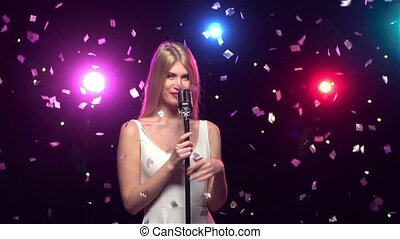 Blonde girl singing into a retro microphone. Slow motion -...