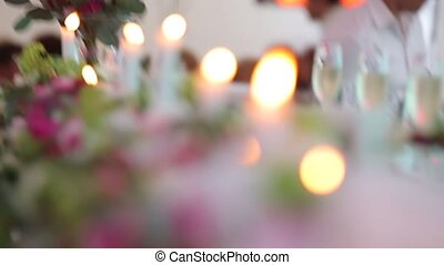Table decor with lighted candles and flowers. Dynamic change of focus. Close up