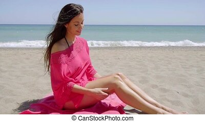 Sexy young woman sitting on a beach on a pink towel wearing...