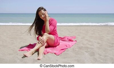 Gorgeous stylish young woman sunbathing on a pink towel on a...