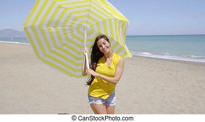 Happy young woman holding a sun umbrella