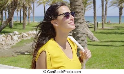 Smiling vivacious young woman in sunglasses and a colorful...
