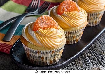 Orange Vanilla Bean Swirled Cupcakes - Row of orange and...