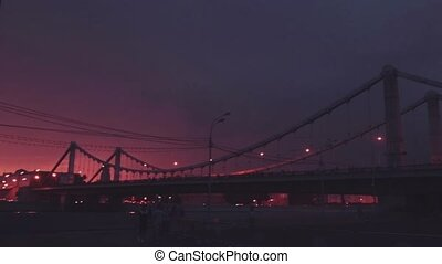 View at dramatic red and black night sky thunder storm. Lighting flash. Bridge. Stormy weather.