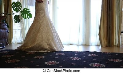 Bride wears a wedding dress in the morning. Bride in the room. Close up