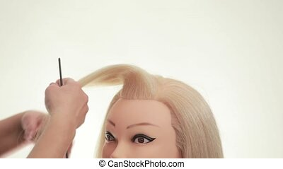 Master demonstrates styling on a mannequin. Mannequin of blonde. White. Close up