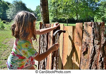 Young girl building fort with hammer and nails. Fun active...