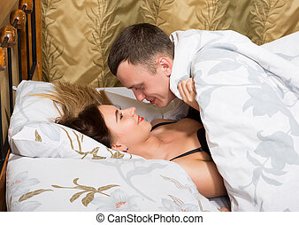 young couple lying on the bed in the hotel. the man leaned...