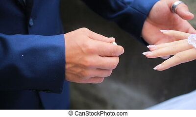 groom wears on the bride's finger a ring
