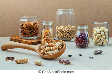 Various beans and nuts in the glass on brown background mung...