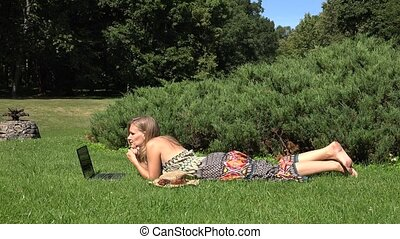 relaxed girl lying on grass in park and work with laptop. 4K...