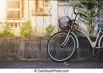 Old bicycle leaning on grunge concrete wall