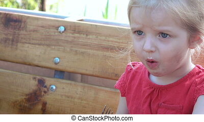 Little girl is naughty behind table - Nature is capricious...