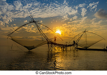 Lifestyle of fishing gear with sunrise at lake, Thailand.