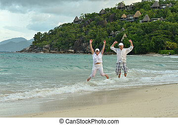 elderly couple jumping at tropical beach - Happy elderly...