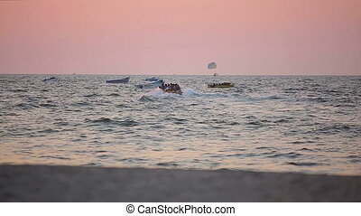 Water activities on the beach at sunset