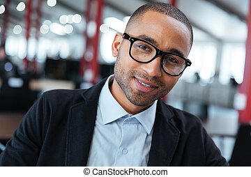 Close-up portrait of a smiling businessman in glasses
